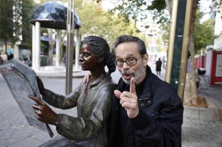Leo Brouwer sentado al lado de una estatuta en Cordova Espana
