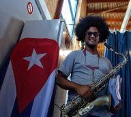 Yuniet Lombida saxofonista con sax y bandera cubana